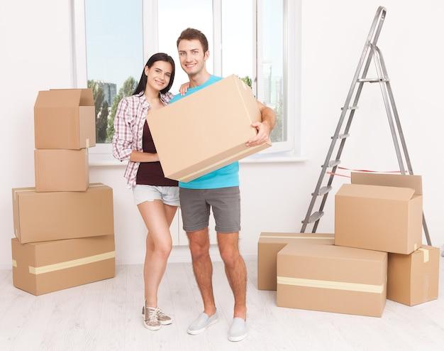 Молодая пара держит большую коробку и счастливо улыбается в камеру