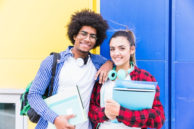 Young couple holding books in hand standing against blue and yellow wall
