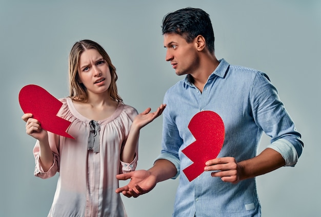 Young couple holding broken heart against grey.