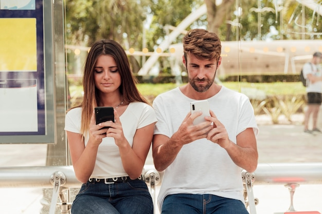 Young couple holding cell phones