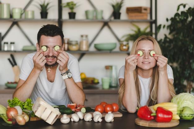 Giovane fetta del cetriolo della tenuta delle coppie sopra gli occhi che stanno dietro il contatore di cucina Foto Gratuite