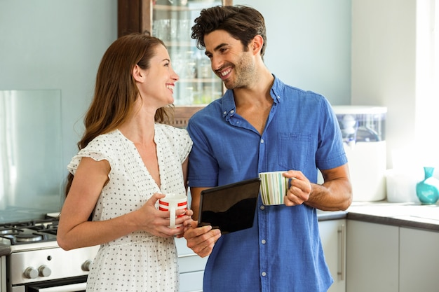 Young couple holding cup of coffee while using digital tablet