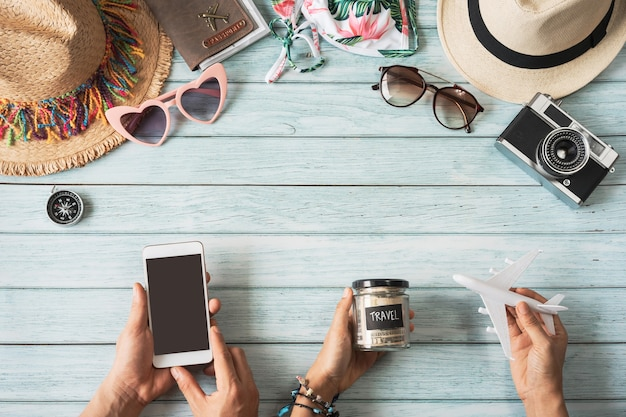Young couple holding empty screen smart phone with travel summer accessories and items on wooden background with copy space, travel planning concept