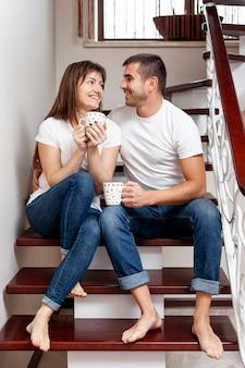 若いカップルが手を繋いでいると階段の上に座って