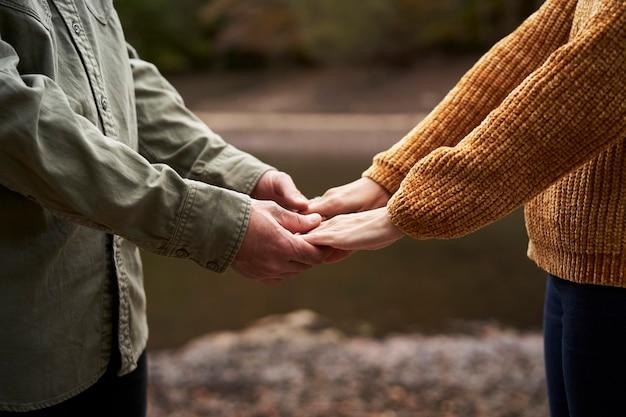 湖で手をつないで若いカップル