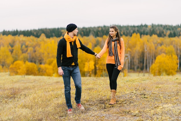 A young couple holding hands on a colorful autumn background