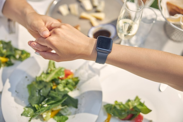 스마트 시계를 착용하는 여자 손 동안 레스토랑에서 날짜를 갖는 손을 잡고 젊은 부부