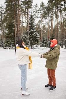Young couple holding hands and learning to skate together on skating rink in winter
