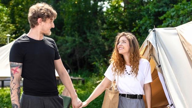 グランピングでテントの近くで手をつないでいる若いカップル。周りの緑