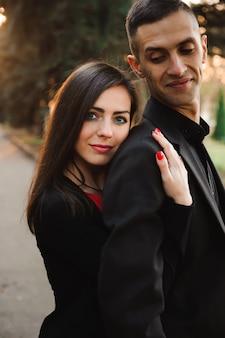 秋の一日に手を繋いでいる若いカップルは、笑顔で公園を散歩します。