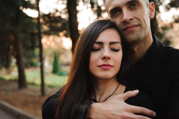 手を繋いでいる若いカップル、笑顔、公園を散歩