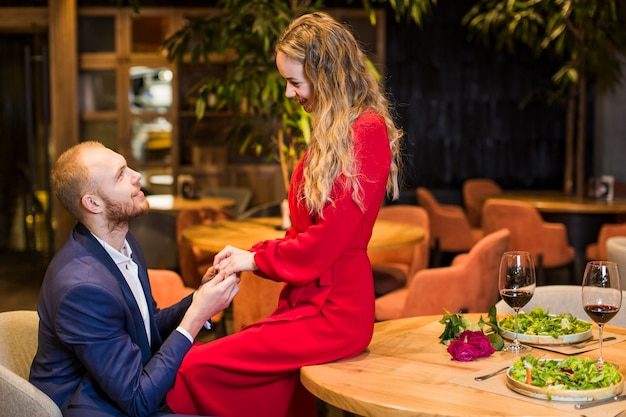 Young couple holding hands at table in restaurant