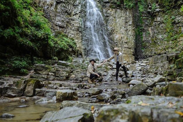 若いカップルが手をつないで、男は石の上に少ししゃがみました。若い男と女が森の小川を渡る。