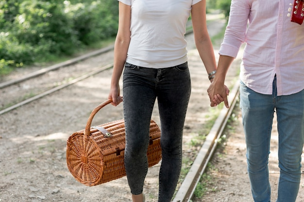 Young couple holding hands and walking on a railroad