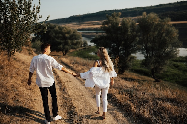 Young couple holding hands and walking through pathway in rural field, smiling and looking each other.