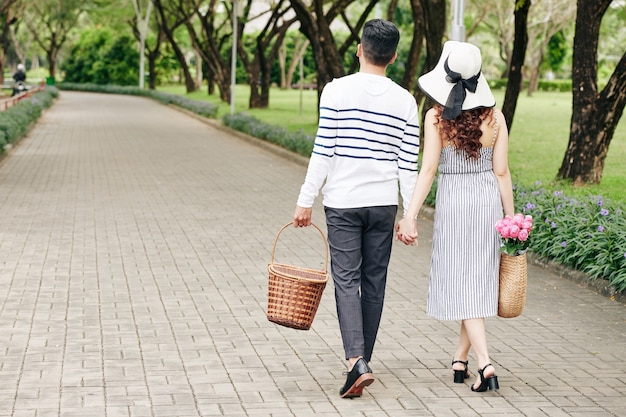 Young couple holding hands when walking in city park with picnic baskets