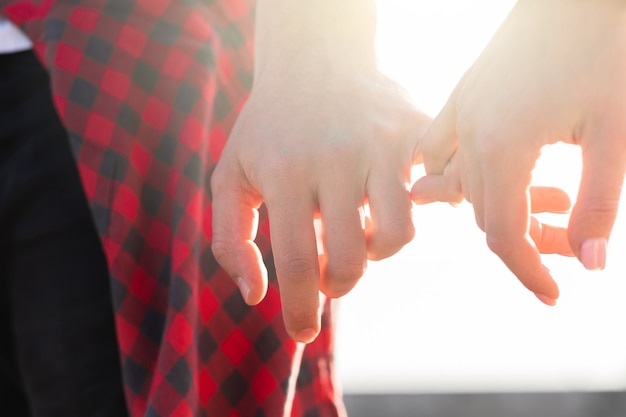 Young couple holding hands with a pinky grip