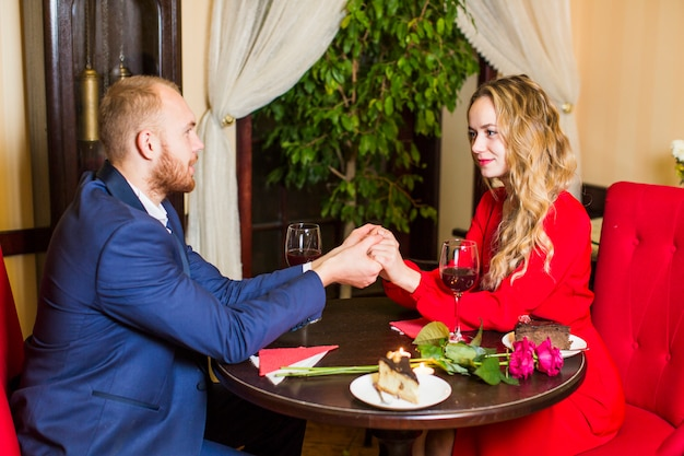 Young couple holding hands at wooden table in restaurant