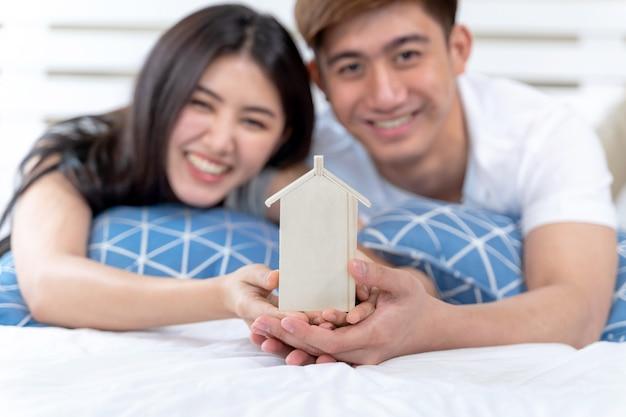 ベッドの上の家のおもちゃを保持している若いカップル