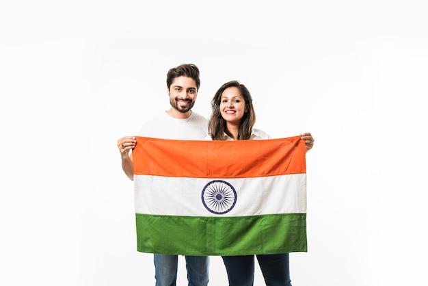 Молодая пара держит индийский флаг в день независимости или республики, стоя изолированным на белом фоне. выборочный фокус
