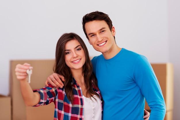 手に鍵を持っている若いカップル