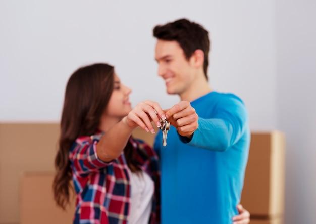 Молодая пара держит в руке ключ от нового дома