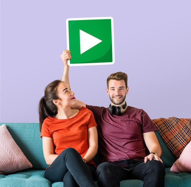 Giovani coppie che tengono un'icona del tasto di riproduzione