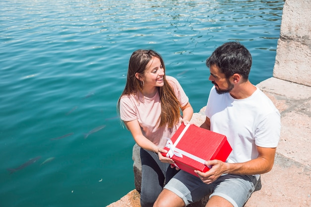 Young couple holding red gift box near sea