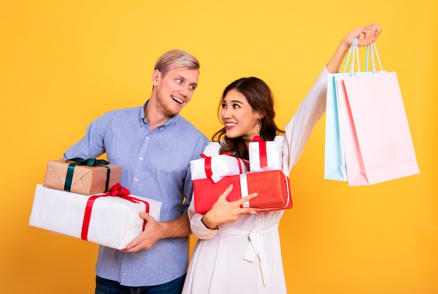 Young couple holding shopping paper bag and gift box on yellow background.