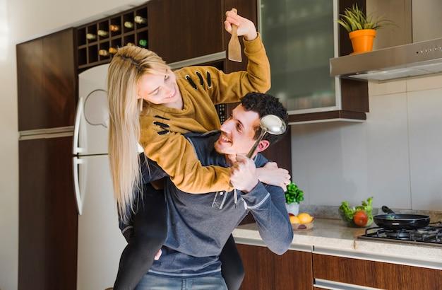スパチュラとレードルが一緒に戦っている若いカップル