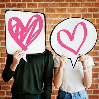 Young couple holding speech bubbles with heart icons