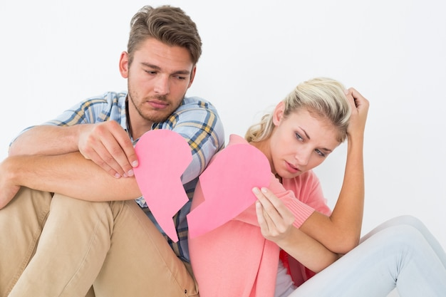 Young couple holding two halves of broken heart