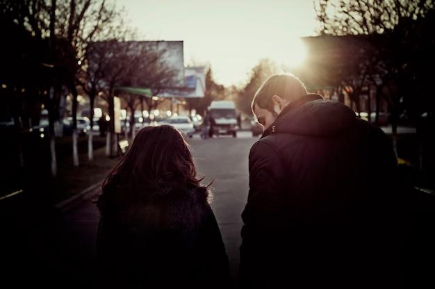 街の通りを歩いて保持している若いカップル