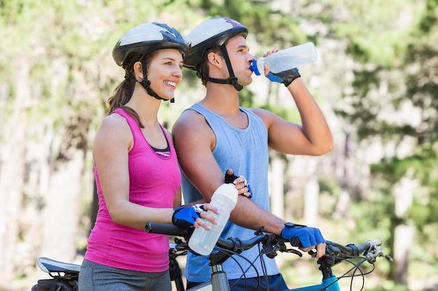 森で水のボトルを保持している若いカップル