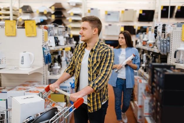 젊은 부부는 전자 제품 매장에서 전기 믹서기를 보유하고 있습니다. 남자와 여자는 시장에서 가전 제품을 구입