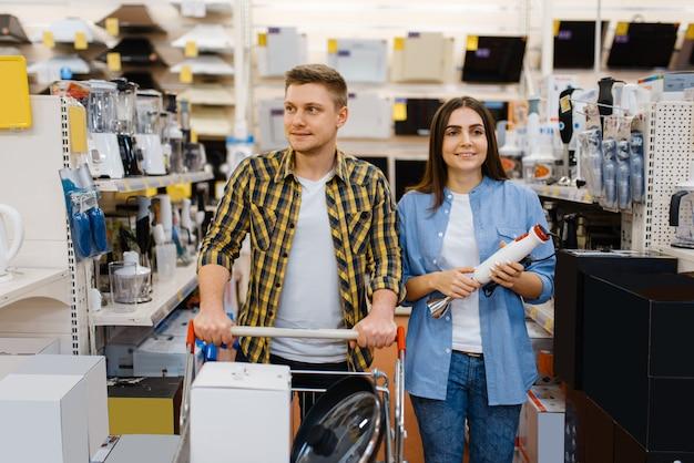 若いカップルは、電気店で電動ブレンダーを保持しています。男と女が市場で家電製品を購入