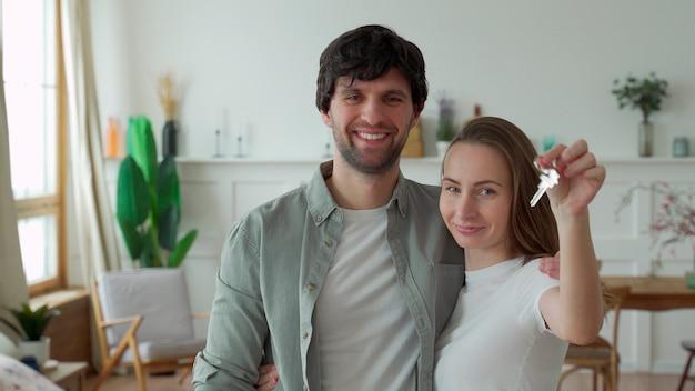 젊은 부부는 행복하게 새로운 가정의 열쇠를 보유하고 있습니다.