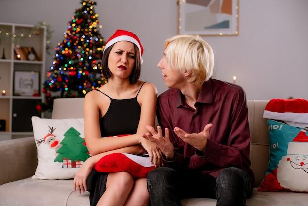 Coppia giovane a casa nel periodo natalizio indossando il cappello della santa seduto sul divano nel soggiorno