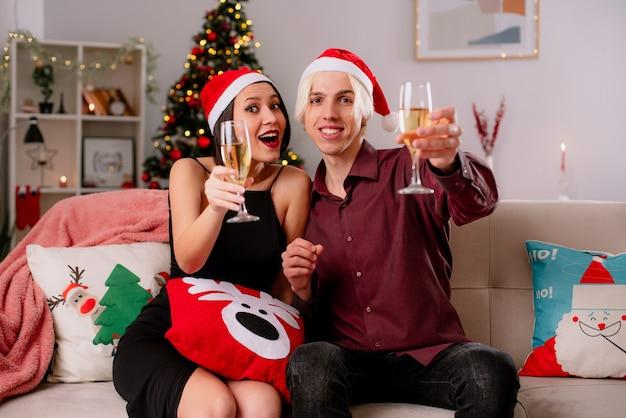 Giovane coppia a casa nel periodo natalizio indossando santa cappello seduto