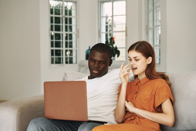 Young couple at home on the couch in front of laptop rest