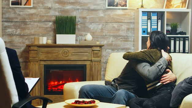 Young couple hug each other sitting on couch at therapy after talking about their difficulties.
