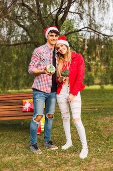 若いカップルがドーナツを共有しながら公園で抱擁