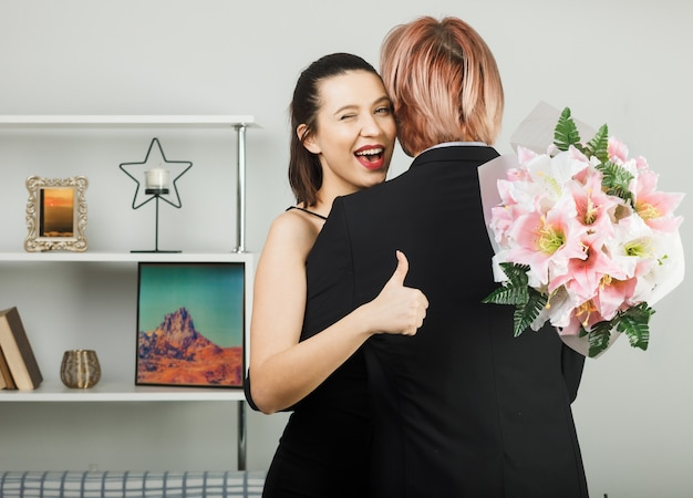 Young couple hugged each other on happy women day with bouquet girl whispers standing in living room