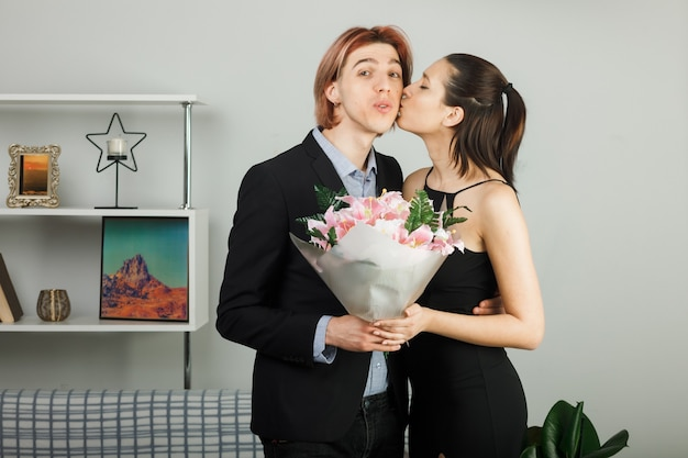 若いカップルは、リビングルームに立っている花束の女性のささやきと幸せな女性の日に抱き合った