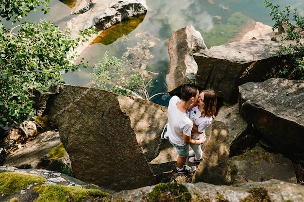 Молодая пара обниматься и целоваться, у камня у озера