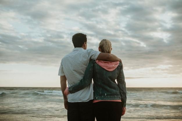 해변에서 포옹 하는 젊은 부부