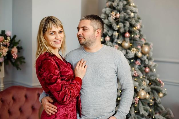 Молодая пара обнимается, обнимается, вместе празднует зимние праздники возле украшенной елки в гостиной .. рождество