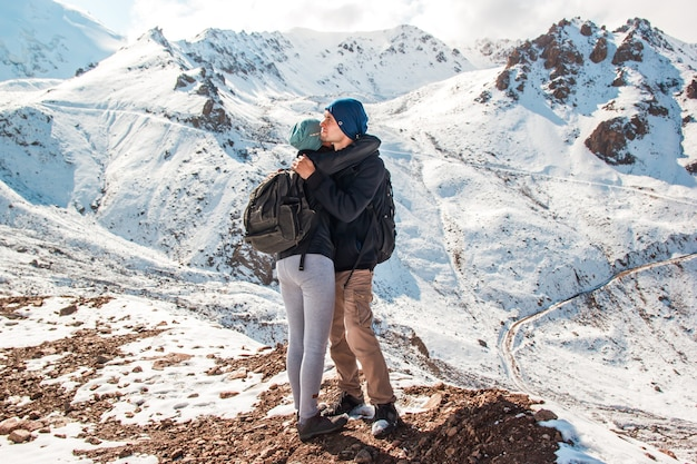 Young couple hugging each other on a background of snowy mountains.