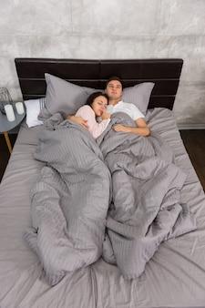 ベッドで寝ている間、灰色のロフトスタイルで寝室でパジャマを着ている間、若いカップルは抱き合っています