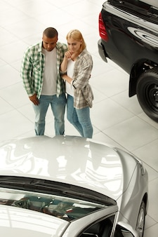 Young couple hugging examining cars at the dealership showroom.